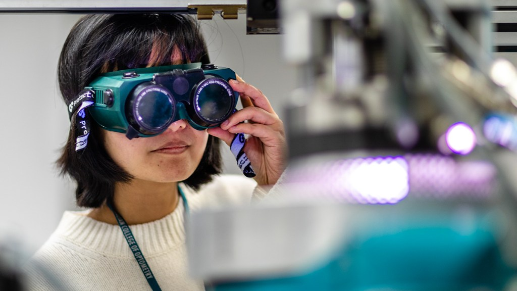 Dr Wei Tong, a member of the Carbon Cybernetics team, holding some special microscope glasses up to work on one of the company's special miniature neural implants.