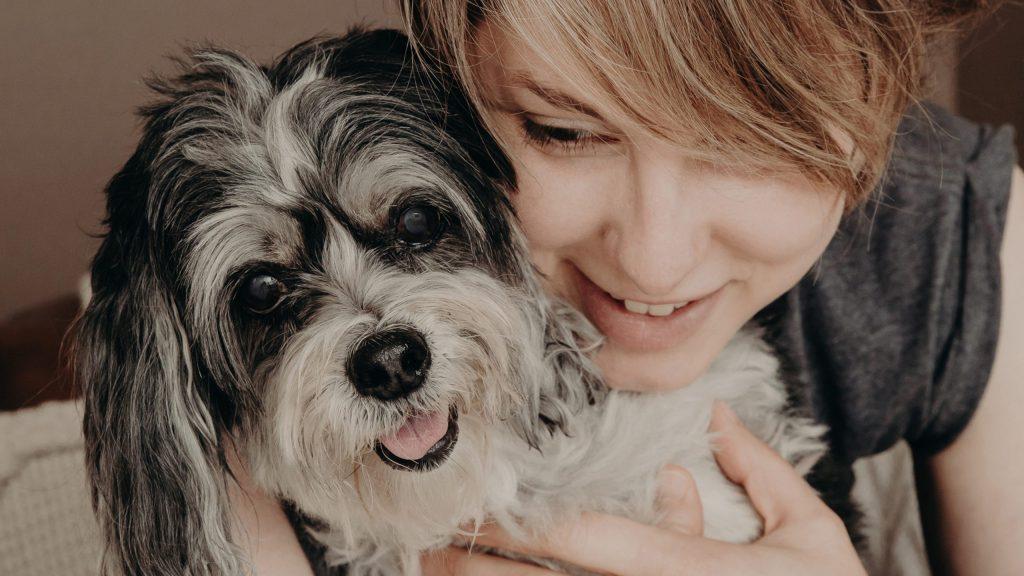 Studio founder Molly Patton embracing her black and white Maltese Shih Tzu Scarlett
