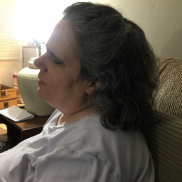A photo of Patty's left profile as she sits comfortably in a chair. She's illuminated by a lamp on the table beside her. Patty has dark hair and is wearing a white t-shirt.