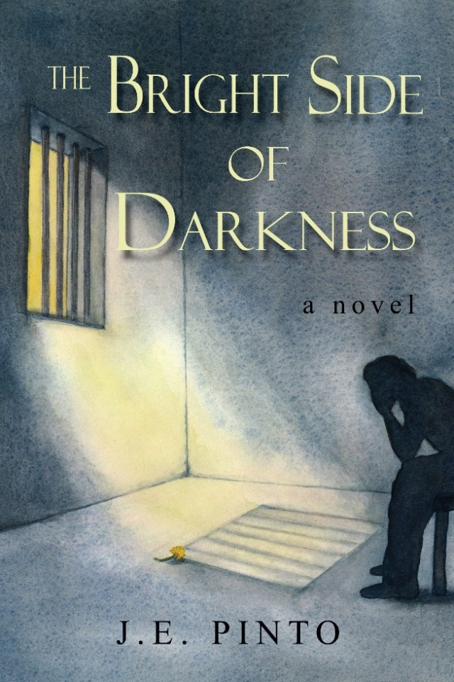 """The illustrated front cover of """"The Bright Side of Darkness: A Novel"""" by J.E. Pinto. A silhouette sits on the right side of the image, their head in their hands and their elbows on their knees. In front of the shadow, light streams in through a square window with vertical bars, creating a striped pattern on the floor. The room is gray and empty apart from the figure and the obstructed light. The title font is crisp, white, capitol lettering with a faint shadow."""