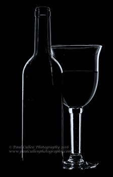 Wine glass and bottle in low light - monochrome with cool blue tones.