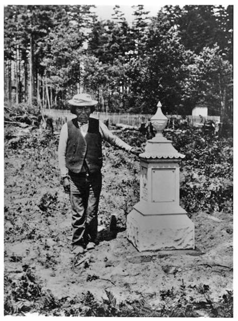 John Cheshiahud stands next to his first wife Lucie Annie's tombstone at Washelli cemetery.