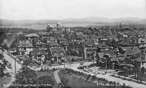 THEN: The Volunteer Park water tower was completed in 1907 on Capitol Hill's highest point in aid the water pressure of its service to the often grand homes of its many nearly new neighbors. The jogging corner of E. Prospect Street and 15th Avenue E. is near the bottom of the Oakes postcard. (Historical Photo courtesy Mike Fairley)