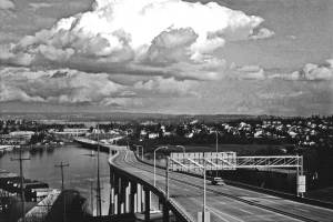 THEN: With great clouds overhead and a landscape 45 years shorter than now, one vehicle – a pickup heading east – gets this part of State Route 520 to itself on a weekday afternoon. (courtesy Lawton Gowey)