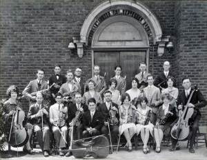 THEN: If I have counted correctly this ca. 1930 Fremont Baptist Orchestra is appointed with three cellos, eleven violins and violas, two saxophones, two clarinets, one coronet, one oboe, one flute and two members who seem to be hiding their instruments. (courtesy Fremont Baptist Church)