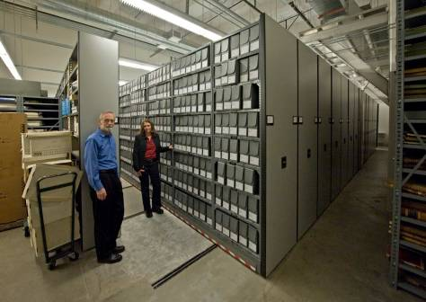 NOW: City archivist Scott Cline, left, and deputy archivist Anne Frantilla look to Jean Sherrard from out of the deep storage of the modern, climate-controlled archives in City Hall.