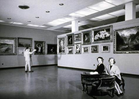 "The main exhibition space in the Frye Art Museum when it opened in 1952.  The picture is a fine example of a ""set-up"" architectural photograph, with the persons chosen, their locations and gestures too.  (Courtesy Frye Art Museum)"
