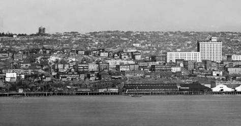 "In this section of a 1908 panorama taken from Duwamish Head both the Moore Theatre and the New Washington Hotel are in place as the front ""hump"" of Denny Hill has been removed.  On the left, however, we can made out the west facade of the Blanchard Apartments clinging above the cliff at Second and Blanchard.  In the distant horizon is the Volunteer standpipe with its exterior brick facade nearly completed."