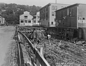 THEN: The work of filling the tidelands south of King Street began in 1853 with the chips from Yesler's sawmill.   Here in the neighborhood of 9th Ave. S. (Airport Way) and Holgate Street, the tideland reclaiming and street regrading continue 70 years later in 1923.  (Courtesy, Municipal Archive)