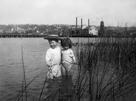 """These two tots in the toolies are the Brown kids.  The father was a plumber and played the clarinet in the popular Wagner's Band.  Western Mill is beyond and Capitol Hill on the horizon.  The Westlake Trestle, before the landfill hear, created this protect southwest corner of the lake, which on the evidence of the Brown negatives - several - was a popular bay for summer sports.  I used this image on the cover of my first """"now and then"""" book.  It has been very very good to me.  (You can inspect/read it in this blogs library or bookstore attached with its own button.  And you can do the same with Vols. 2 & 3 and several more books."""