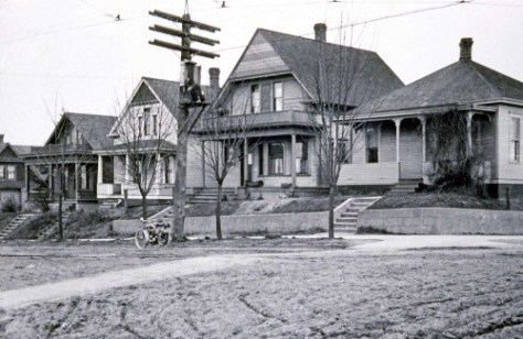THEN: This row of homes, right to left, from 2104 to 2110 7th Ave. West were built in 1905-6, and so they are, by some calibrations, antiques. They are well cared for Queen Anne Hill pioneers.  (Courtesy, Lawton Gowey)