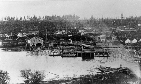 Looking east across the south end of Lake Union to most of an early Western Mill, and perhaps the oldest photograph of it, ca. 1884.  Capitol HIll is on the horizon.