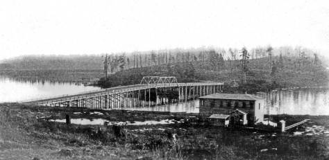 THEN: The Latona Bridge was constructed in 1891 along the future line of the Lake Washington Ship Canal Bridge.  The photo was taken from the Seattle Lake Shore and Eastern Railway right-of-way, now the Burke Gilman Recreation Trail. The Northlake Apartment/Hotel on the right survived and struggled into the 1960s.  (Courtesy, Ron Edge)