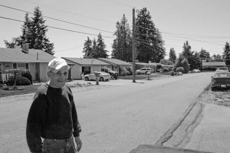 Midget racer Mel Anthony, inducted into the Golden Wheels Hall of Fame in 2002, stands on the pavement of Edmonds' 82nd Ave. West, a few yards south of 230th Street Southwest, and so repeating the historical view, above, of the Speed Bowl.