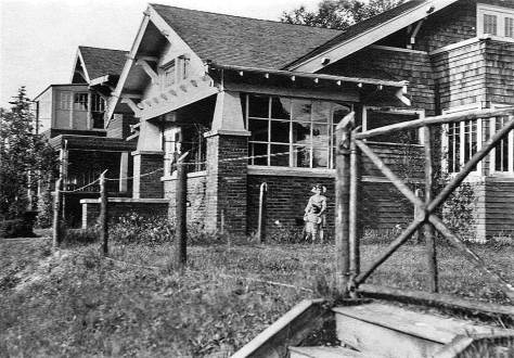 THEN: The Craftsman bungalow at 1910 47th Ave. S.W., shown in the 1920s with an unknown adult on the porch and two tykes below, is now 100 years old. The house beyond it at the southeast corner with Holgate Street was for many years clubhouse to the West Seattle Community Club, and so a favorite venue for discussing neighborhood politics and playing bridge. (COURTESY OF SOUTHWEST SEATTLE HISTORICAL SOCIETY)