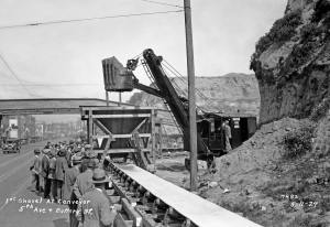 "THEN: Before this the first shovel of the last of Denny Hill was ceremonially dropped to the conveyor belt at Battery Street, an ""initial bite of 30,000 cubic yards of material"" was carved from the cliff along the east side of 5th Avenue to make room for both the steam shovel and several moveable belts that extended like fingers across the hill. It was here that they met the elevated and fixed last leg of the conveyor system that ran west on Battery Street to the waterfront. (Courtesy, Seattle Municipal Archive)"