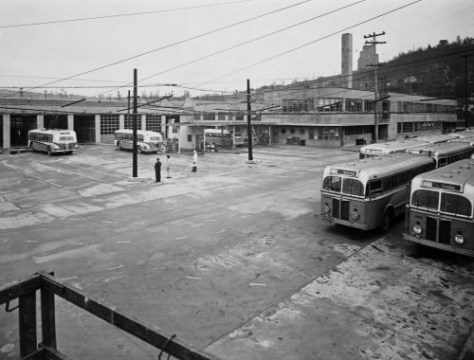 Both near busses and trackless trollies at the Muni. Bus barn.  The view looks east on the garage's parking lot somewhat in line  with Atlantic Street.  Railroad Ave. (aka 9th Avenue) is on the other side of the buildings, and the Marine Hospital is on the Beacon Hill horizon. (Courtesy, MOHAI)