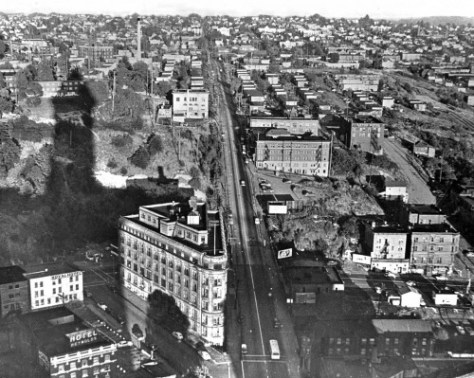 The Smith Tower casts its shadow up the rough terrain of Goat Hill.   Yesler Way splits the landscape.