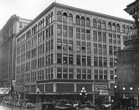 A kitty-korner look at the Ranke Bldg with the same sidewalk businesses.   Far right is glimpse of the Coliseum Theatre, and far left the Seaboard Building, all still standing.