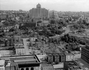 THEN: On his visit to the Smith Tower around 1960, Wade Stevenson recorded the western slope of First Hill showing Harborview Hospital and part of Yesler Terrace at the top between 7th and 9th Avenue but still little development in the two blocks between 7th and 5th Avenues. Soon the Seattle Freeway would create a concrete ditch between 7th and 6th (the curving Avenue that runs left-to-right through the middle of the subject.) Much of the wild and spring fed landscape between 6th and 5th near the bottom of the revealing subject was cleared for parking. (Photo by Wade Stevenson, courtesy of Noel Holley)