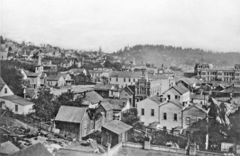 The front facade of the fire station on Columbia appears near the center of this look south into Seattle's oldest neighborhood from the roof of the Frye Opera House at Front (First Ave) and Marion Street, ca. 1886.  The ornate Occidental Hotel appears far right, and Beacon Hill, much of it still forested, on the horizon.
