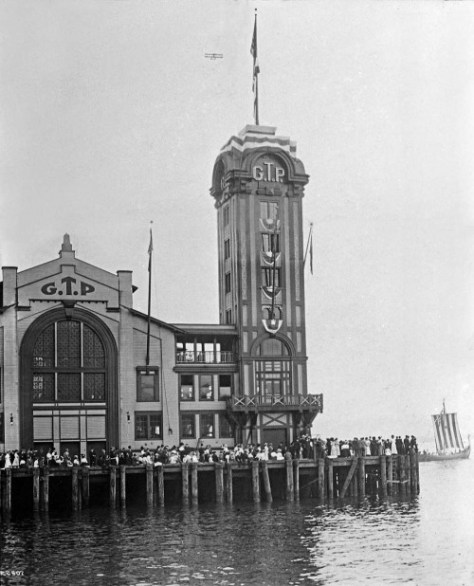 The Grand Trunk Pier in 1911 during the celebration of Seattle's first staging of the Golden Potlatch Days, the city's first multi-day summer festival.   A highlight were the aeroplane antics overhead. (Courtesy Michael Maslan)