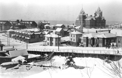 Central School, on the right, and the Rainier Hotel, on the left, photographed during an unidentified snow from the 1890s.  The photographer stood on 8th Ave. south of Columbia Street.   Had the camera been turned a few degrees to the left, it would have included some of the Fire Dept. Headquarters.