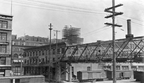 Looking across Railroad Avenue from the open second floor portico of the then brand new Grand Trunk pier, Phillip Hughett's snapshot form late 1910 or early 1911 reaches from the Maritime building on the left to nearly new Marion Street overpass on the right.    His intended subject at the scene's center skyline is the just topped-off steel skeleton of the Hoge Building still at Second Avenue and Cherry Street. (Picture courtesy of Jim Westall)