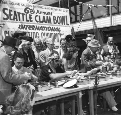 A scene from one of the Acres of Clams Clam Eating Contests stage on a barge while sharing the slip on the south side of Pier 54 with the fire boats.