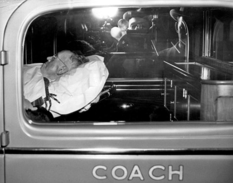 The sick mayor flashed thru the coach's window by a press photographer with a self-portrait with camera reflected in the far window.