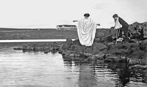 A nurse - or angel - with Buerger's disease victim on the here rocky shore of Soap Lake with a hospital on the horizon.