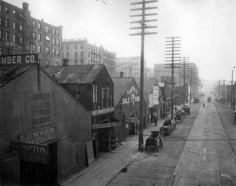 Another A. Curtis record, this one looking south on Western Avenue from the University Street ramp.  The south end of the rank of hotels that crowd the west side of First Avenue between University and Seneca Streets rise above the narrow block of warehouse and manufacturing sheds that fill the block between Western and Post Alley (aka Post Avenue.)