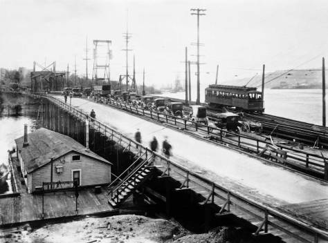 Perhaps it (may be) likely that this record of the bridge was taken by the same Municipal photographer on the same day from the Paysee Hardware Store.  The trio of bridges are used the same as in the featured photograph, and the line-up of motorcars behind the truck may be compared by, for instance, the size of their rooftops.  (Courtesy Municipal Archive)