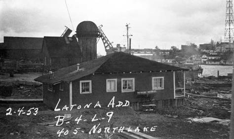 A Feb. 4, 1953 tax photo looking east thru the Wayland mill site from the foot of 4th Avenue n.e. on Northlake.  The mill's burning tower is obvious center-right and beyond it to the east the open bascules of the University Bridge.