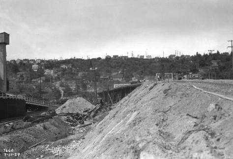 With a glimpse of the steel mill on the far left, here Spokane Street is being reshaped a lifted above fill.  The view looks west on July 11, 1929.  (Courtesy, Seattle Municipal Archive)