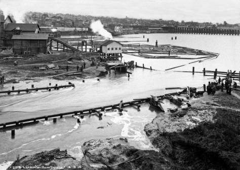 THEN: From the Fremont Bridge, this subject looks northwest across the torrent that followed the washout of the Fremont Dam in the early afternoon of March 13, 1914. Part of the Bryant Lumber and Shingle Mill appears left-of-center. The north end of the Stone Way Trestle appears in the upper right corner. (Courtesy, Seattle Municipal Archives)