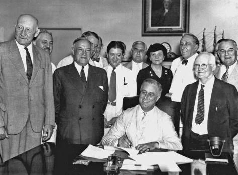 The August 14,1935 signing of the Social Security bill, with FDR in saintly white and smiling.