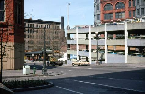 "A sideview of the Sinking Ship Garage by Lawton Gowey on April 21, 1976.  The ""basket handle"" windows on the garage's top level may be compared to their inspiration, the arched windows in the Pioneer Building beyond the garage."