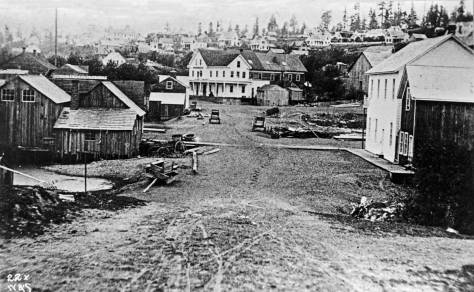 North on Occidental ca. 1872.  In truth the avenue was then still named Second.  Note the big puddle to the left.  When the first settlers first arrived on this side of Ellliott Bay in 1852, this covered by the tides more often than not.