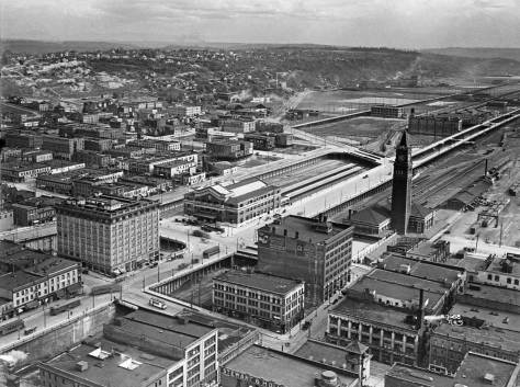 The developing tideflats and the Great Northern and Union Pacific stations on Jackson Street.  The tower of the fire station at the northwest corner of Main Street and Third Avenue is seen near the bottom of the photograph, right-of-center.