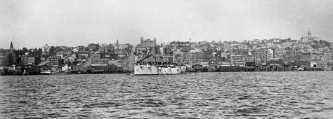 F. J. Haynes look at the waterfront from a vessel on Elliott Bay.  Madison Street is just left of the bright navy vessel at the center.  On the horizon above it is Central School at the southeast corner of 6th and Madison.  Is it brand new.  And so it the King County Court House on the horizon, far right.  (Courtesy Tacoma Pubic Library)