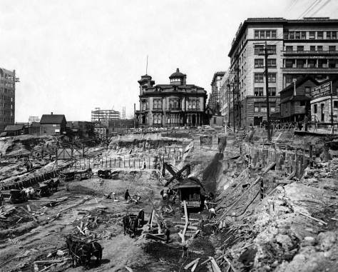 THEN: Looking north from Columbia Street over the construction pit for the Central Building. On the left is a rough section of the Third Avenue Regrade in the spring of 1907. (Courtesy, MOHAI)