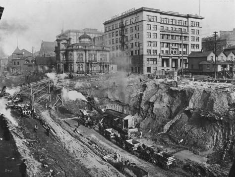 The Third Ave. regrade with the Marion Street pedestrian trestle on the left, the Stacy mansion, left of center, and the Standler Hotel, right of center.  Foundation work for the Central Building has yet to begin.  Note the Third Ave. Theatre with its full top, far-left.