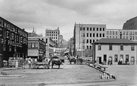 Columbia Street looking west from the waterfront in the first year following the 1889 fire.  The new Seattle Lake Shore and Eastern depot is on the right, and the rear facade of the new Toklas and Singerman Department Sore rise five stories behind it. Photo taken by the Nothern Pacific Railroad's official photographer, F. J. Haynes. (Courtesy, Tacoma Public Library and Murray Morgan)