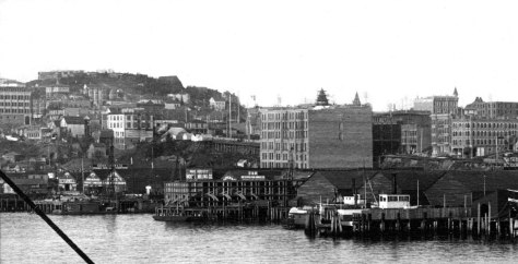 Three Hotels - of note - following the Great Fire of 1889, here in 1890.  First on top of Denny Hill the Denny Hotel (later renamed the Washington) is under construction.  Next, at the center of this detail from a pan taken from the King Street coal wharf stands the undecorated south and west facades of the Arlington Hotel, and its tower at the northeast corner of the building but at the southwest corner of First Ave. and University Street rises from it.  The tower was later removed.  Next, the Ripley Hotel under late construction at the far left.   Also note the dark coal wharf at the foot of Madison Street.  Its place is now part of Ivar's Pier 54 which for another 200-plus days will be remodeling as they rebuild the seawall at its front door.