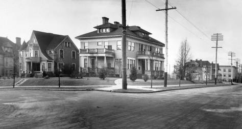 THEN:  This detail from the prolific local photographer Asahel Curtis's photograph of the Smith/Rininger home at the northwest corner of Columbia Street and Summit Avenue dates from the early twentieth century when motorcars, rolling or parked, were still very rare on the streets of Seattle, including these on First Hill.  (Courtesy, Historic Seattle)