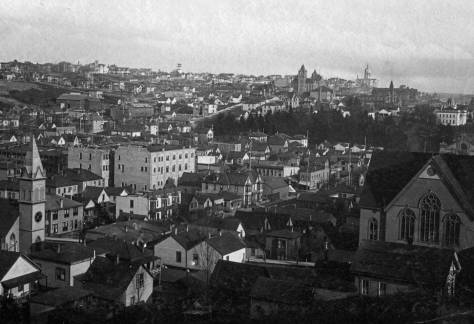 "Fourth Avenue between Pine and Pike Streets begins, in this ""birdseye"" from Denny Hill, to the right of the Lutheran church with the steeple, far left, right to the intersection with Pike, which is just right-of-center.  The structures on the east side of Fourth Avenue seen here in the 1890s match those in the feature photo.  The Methodist Protestant church, on the right, is at the southeast corner of Third Ave. and Pine Street.   The larger light brick building, left of center, is named for its builders/owner, Otto Ranke."