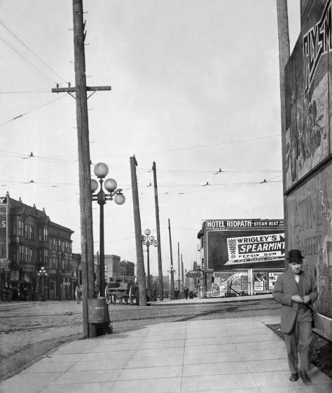 """THEN: In 1910, a circa date for this look north on First Avenue across Virginia Street, the two corners on the east side of the intersection were still undeveloped – except for signs. The Terminal Sales Building, seen far right in Jean Sherrard's repeat, did not replace the billboards that crowd the sidewalk in the """"then"""" until 1923. (Seattle Municipal Archive)"""
