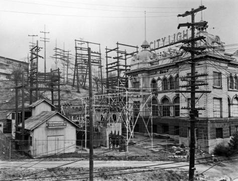 City Light's sub-station on the north side of Yesler Way at the west side of 7th Ave. (now over the freeway pit) in a photo not by Frasch but by a city photographer who has dated it Jan. 20, 1914 at the bottom right corner.  In the City Light link included below, you will find an attached feature on this sub-station with an earlier photo of it.