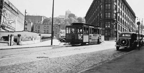 Here's a THEN of the same intersection, which moves closer to Jean's position, or reaches beyond it to the sidewalk for a look up Terrace Street, or rather an impression of it through the windows of the Yesler Way Cable car which in this ca. 1940 shot is about on its last cable.  (Courtesy Lawton Gowey)